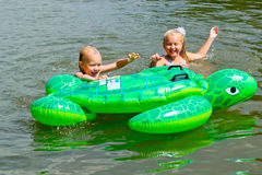 游泳在有可膨胀的tur的河的孩子 免版税库存照片