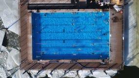 游泳在水池的人们在冬天顶视图角度 免版税库存照片