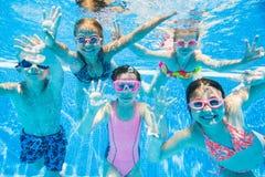 游泳在水池的小孩在水面下 免版税库存照片