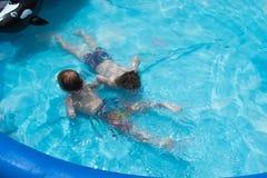 游泳在水面下在后院游泳池的两个男孩 免版税库存照片