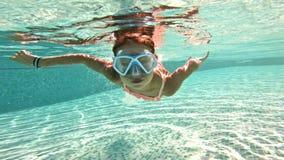 游泳在水面下在水池的女孩佩带的潜航的面具 股票录像