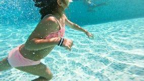 游泳在水面下在水池的女孩佩带的潜航的面具 股票视频