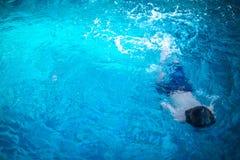 游泳在水面下在水池的小孩 免版税库存照片
