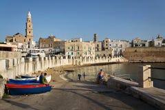游泳在海滩波尔塔Vecchia的人们在大教堂附近在日出期间在Monopoli,意大利 库存图片