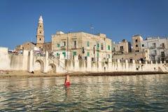 游泳在海滩波尔塔Vecchia的人们在大教堂附近在日出期间在Monopoli,意大利 免版税库存图片