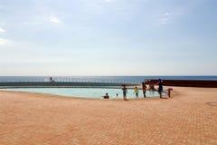 游泳在海边水池的人们反对海洋地平线 库存图片