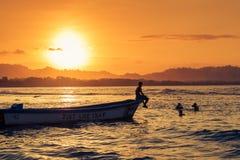 游泳在海滩的人们在Puerto Viejo de塔拉曼卡,哥斯达黎加,在日落 免版税图库摄影