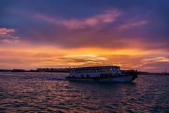游泳在男性镇,日落的马尔代夫附近的地方轮渡 免版税图库摄影