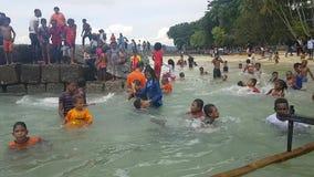 游泳在衣裳的孩子由在Mansinam的海滩 影视素材