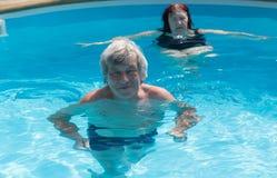 游泳在水池的前辈 图库摄影