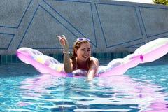 游泳在水池的床垫的妇女佩带的太阳镜和比基尼泳装姿势 海岛普吉岛泰国 免版税库存图片