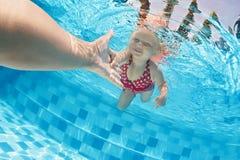 游泳在水面下在与父母的水池的孩子 库存照片