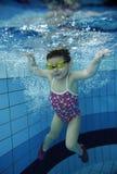游泳在水面下在与许多的一个水池的滑稽的愉快的小孩女孩气泡 免版税库存照片
