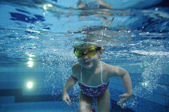 游泳在水面下在与许多的一个水池的滑稽的愉快的小孩女孩气泡 图库摄影