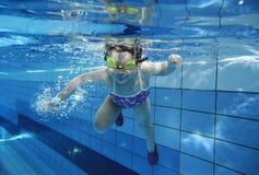 游泳在水面下在与许多的一个水池的滑稽的愉快的小孩女孩气泡 免版税库存图片