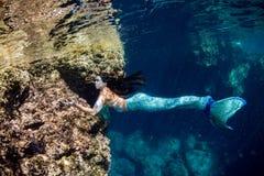 游泳在水面下在深蓝色海的美人鱼 库存图片
