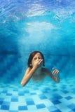 游泳在水面下在蓝色水池的小男孩 免版税图库摄影