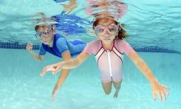 游泳在水面下在水池的两个孩子 免版税图库摄影