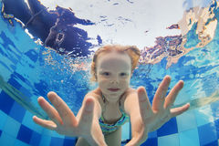 游泳在水面下在水池的女婴滑稽的画象 免版税库存图片