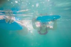 游泳在水面下在水池的逗人喜爱的孩子 库存照片