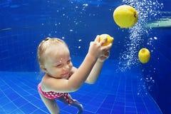 游泳在水面下在黄色柠檬的蓝色水池的孩子 库存图片