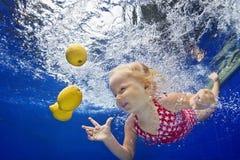 游泳在水面下在黄色柠檬的蓝色水池的孩子 图库摄影