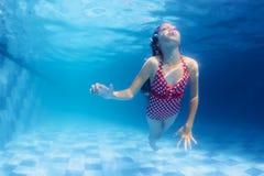 游泳女孩在蓝色水池潜水在水面下 库存照片