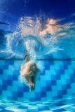 游泳女孩在蓝色水池跳深下来在水面下 库存图片