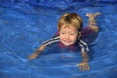 游泳教训:逗人喜爱的女婴n水池 免版税图库摄影