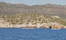 游泳有游人的游船在船上 免版税库存照片