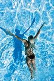 游泳水下的妇女的池 免版税库存图片