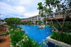 游泳池、大象喷泉、太阳懒人在庭院旁边和大厦 免版税库存图片