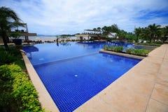 游泳池、太阳懒人在庭院旁边和塔咖啡馆 免版税库存图片
