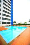 游泳池、太阳懒人在庭院旁边和塔大厦 免版税库存图片