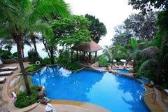 游泳池、太阳懒人在庭院旁边和塔海的 免版税库存图片