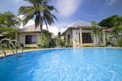 游泳池、太阳懒人在庭院旁边和塔 免版税库存照片