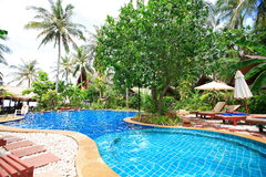 游泳池、太阳懒人在庭院旁边和塔 免版税库存图片