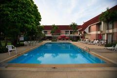 游泳池、太阳懒人在庭院旁边和大厦 库存图片