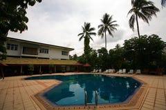 游泳池、太阳懒人在庭院旁边和大厦 免版税图库摄影