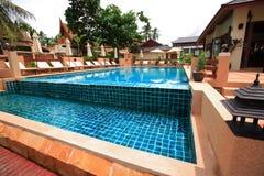 游泳池、太阳懒人在庭院旁边和大厦 免版税库存照片