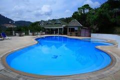 游泳池、太阳懒人在庭院旁边和平房 图库摄影