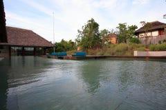 游泳池、太阳懒人在庭院旁边和平房 免版税库存照片