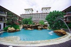 游泳池、太阳懒人在庭院旁边和殖民地大厦样式 免版税库存图片