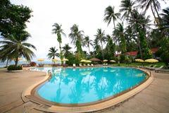 游泳池、太阳懒人在庭院旁边和海地平线 免版税图库摄影