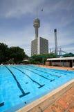 游泳池、太阳懒人在庭院旁边和高大厦 免版税库存照片