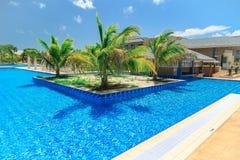 游泳池、平静的绿松石天蓝色的水和热带庭院邀请的出色的意见  免版税库存照片