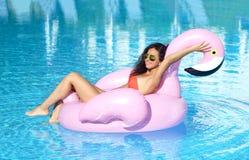 游泳池休闲的妇女在红色比基尼泳装的一个巨型可膨胀的巨型桃红色火鸟浮游物床垫 免版税图库摄影