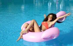 游泳池休闲的妇女在红色比基尼泳装的一个巨型可膨胀的巨型桃红色火鸟浮游物床垫 库存照片