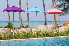 游泳池和海滩睡椅在海,泰国附近 免版税库存照片