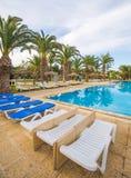 游泳池和轻便折叠躺椅在豪华旅游胜地 免版税图库摄影